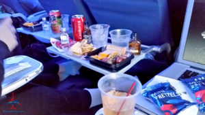 Jack Daniel's, Woodford Reserve, Finlandia vodka, Coca-Cola, fruit and cheese platters, and assorted other snacks are seen onboard a Delta flight from New York (JFK) to Los Angeles International Airport (LAX). ©RenesPoints.com