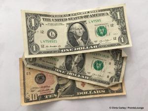One ten dollar bill and two one dollar bills.