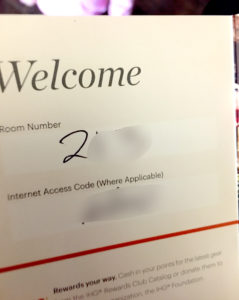 An IHG hotel key packet with room number.