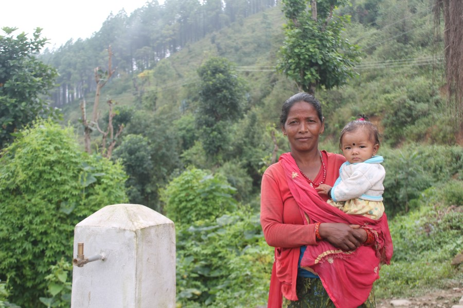 Chandra Kauli Sunar, A Nepali lady standing next to a water tap holding he young granddaughter