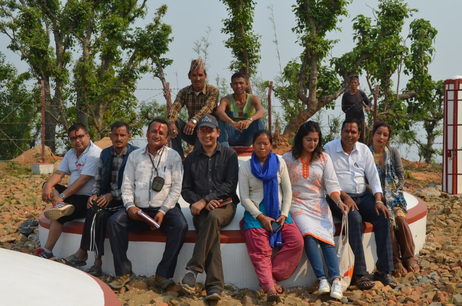 A group of community members smiling and sitting on one of the round water tanks.