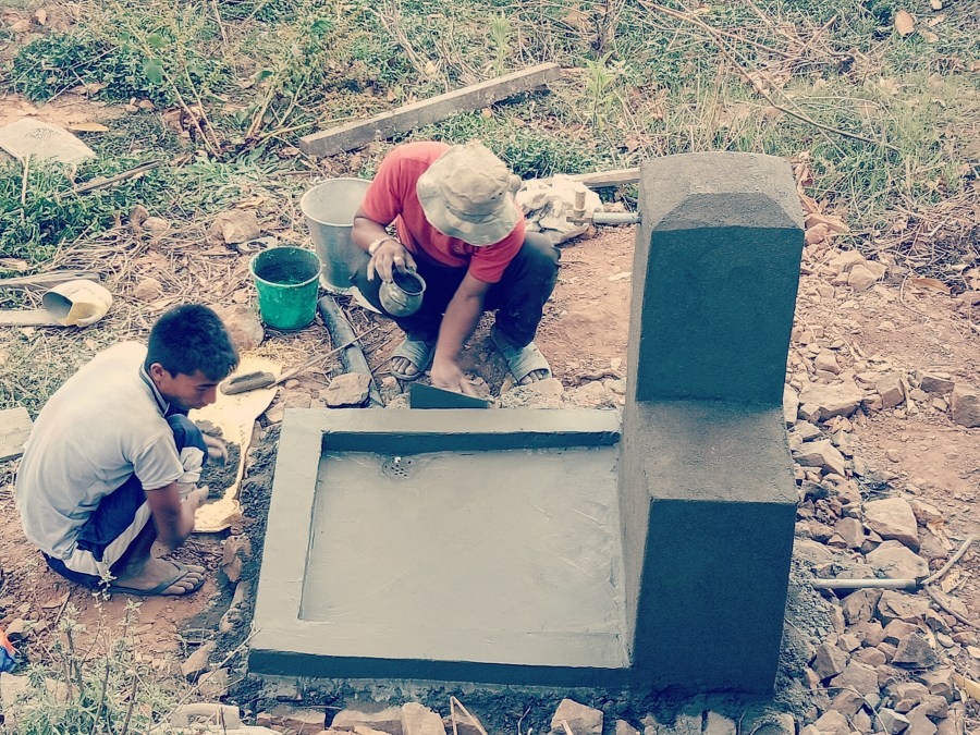 Two masons constructing a water thank with water collection point