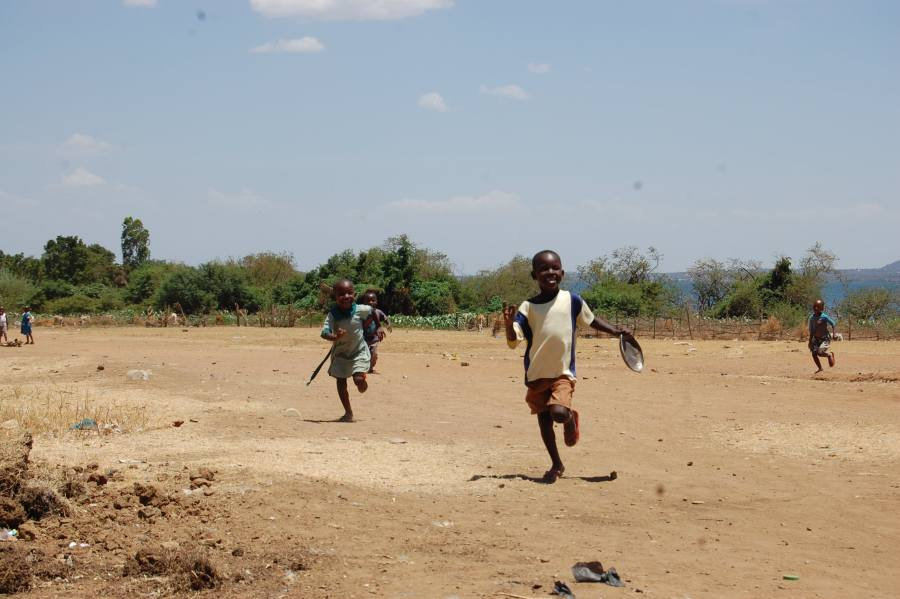 Four smiling children running towards the camera. The ground is dry and dusty, the sky is blue and clear