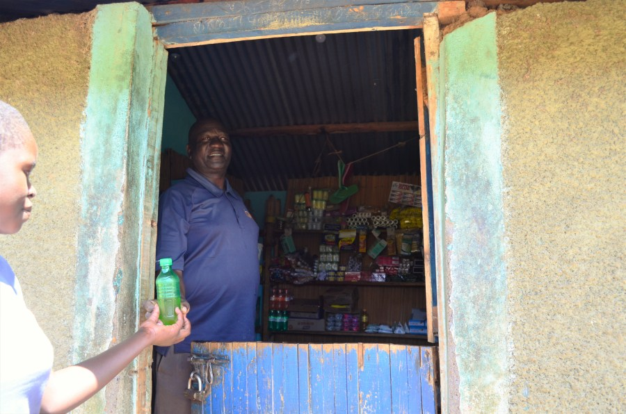 Pascal standing in his store serving a customer. Biscuits, crisps, soap and other items for sale can be seen behind him.