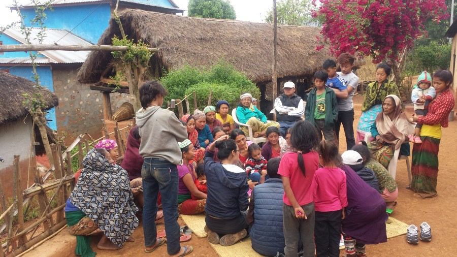 A community meeting taking place outside in front of houses in Magare