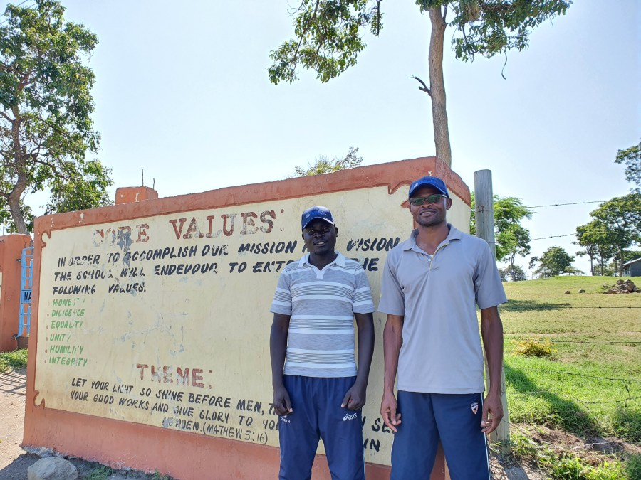 Fred, the deputy head pictured on the left, standing outside the school gates. He is now completing a distance learning course in Business Administration, which will help him to better support the school going forward