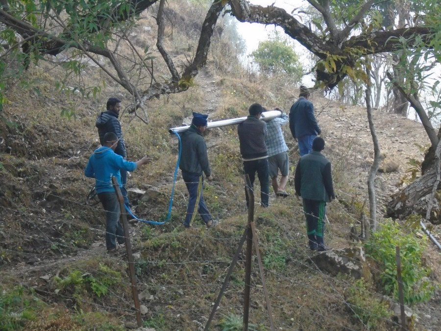Three men carrying one the sections of the pipe to the top of the hill, as other community members help out.