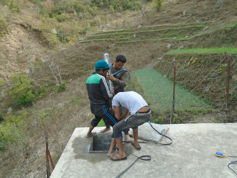 Three men install the solar-powered pump on a platform on a hill in the community.
