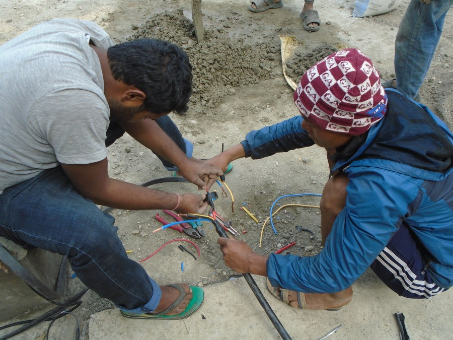 Two men work together on Intricate and careful wiring for the pump.