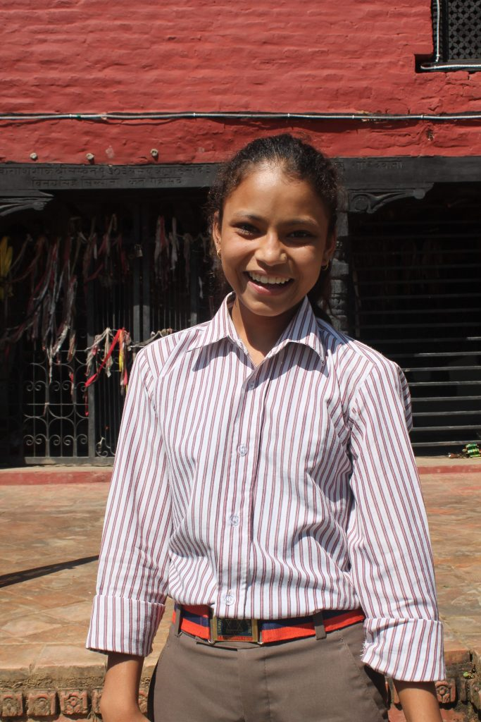 Deepa smiling in front of the school.