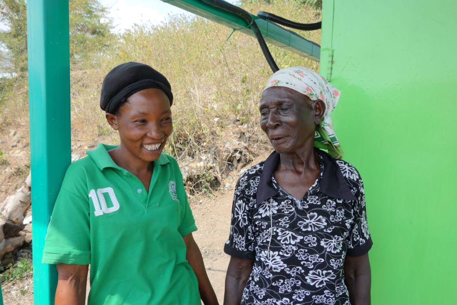 Diana smiling in front of the energy hub with a member of the community.