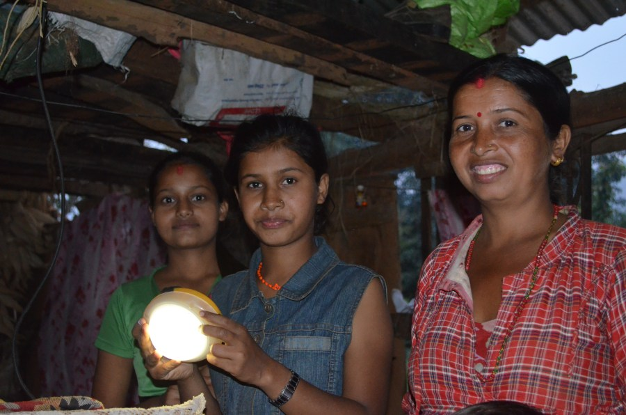 A young girl and her family with a solar-light that they received from Renewable World as part of the Earthquake Relief project