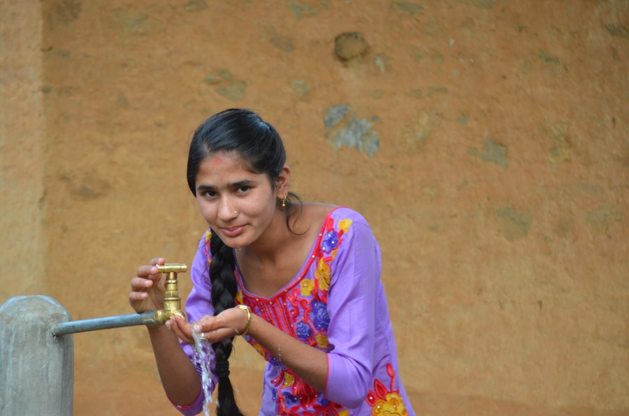Sushmita using the new tap in her village in Nepal.