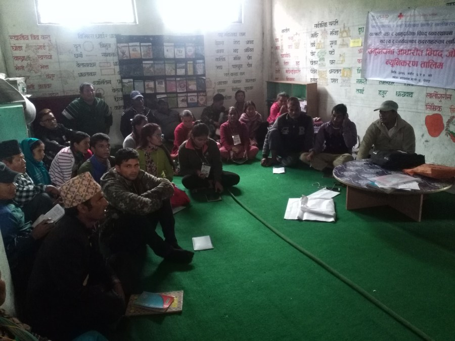 Community members sat on the ground in a room receiving training