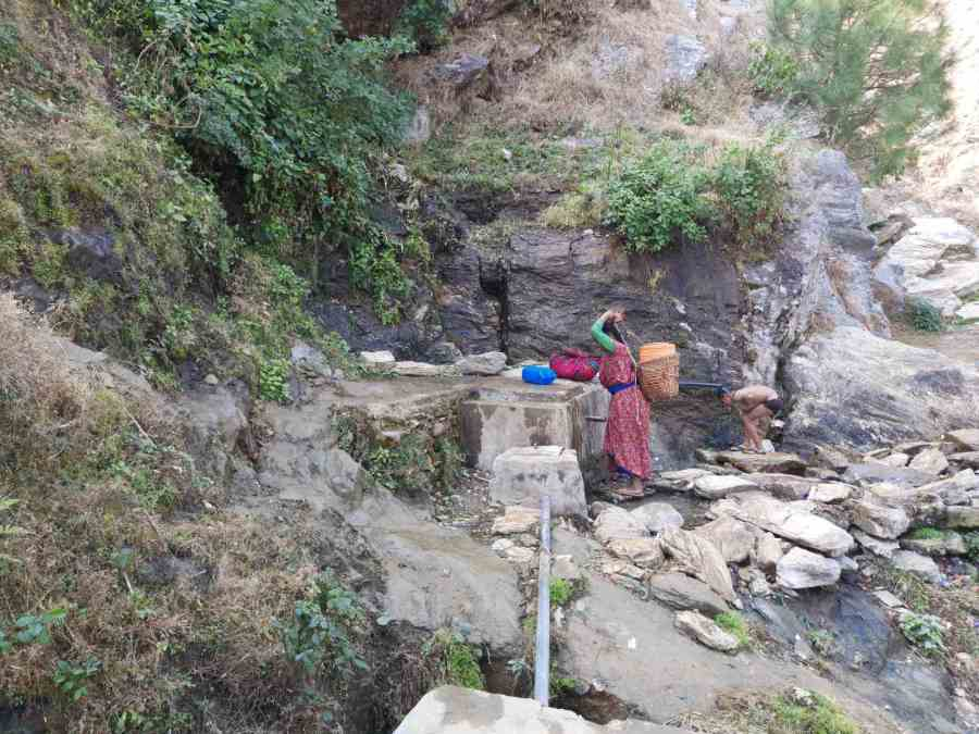 A woman fetching water from the source closest to Layati village.