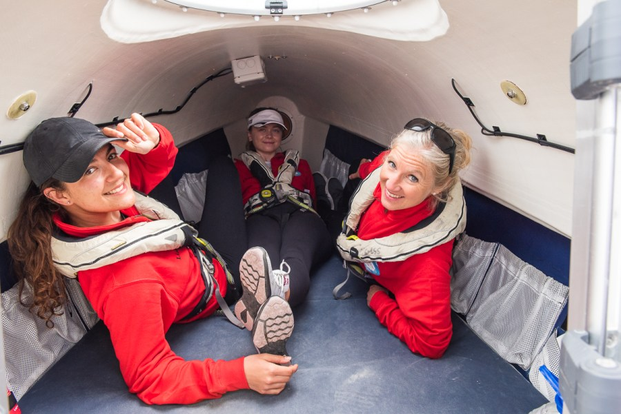 Three members of All Systems row lying down in the boat's sleeping quarters (there's not much room in there!)