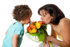 Toddler girl giving flowers to her mom on mother's day