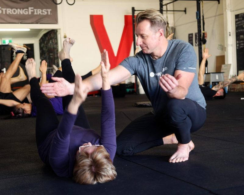 Male PT helping 50+ female with a core exercise