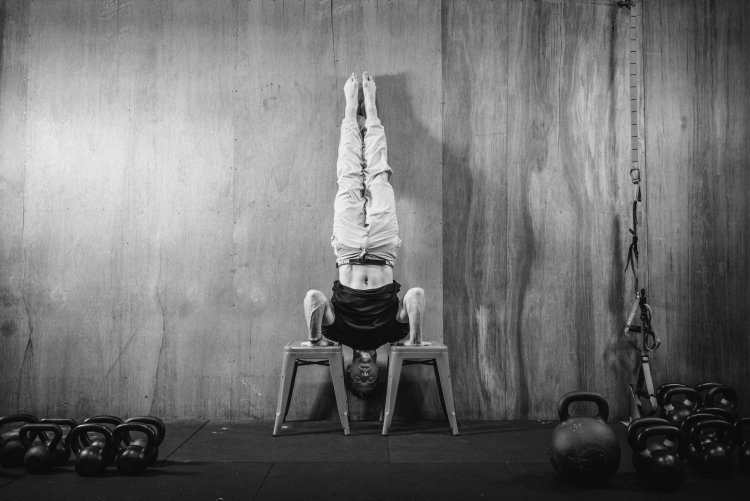 black and white picture of a man doing a handstand against a wall on two chairs (Aleks Salkin)