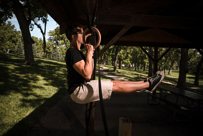 picture of a man in a undercover outdoor area doing an l-sit pullup on olympic rings