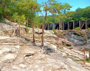 The railing and steps lead down to the overlook, providing a view back at the dam, as well as the upper and lower falls