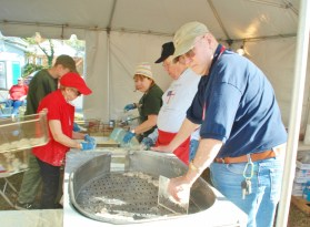 Oysters poured from the gallon containers are drained before going to the breading table.