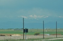 Snow-covered mountains emerge out of the distant haze.