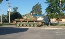 A surplus military tank is parked by the convenience store across Rt 36 from the park.