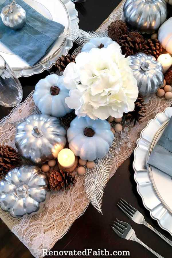 Thanksgiving Tablescape with Blue Pumpkins – Want an elegant centerpiece on a budget? Paint dollar store pumpkins in blue and silver for a traditional tablescape with a modern flair. The use of natural pine cones and burlap add some vintage style to contrast the glam of the silver pumpkins. This easy fall décor shows that simple and beautiful centerpieces don't have to be expensive. #fall #thanksgiving #centerpiece #pumpkins #bluepumpkins #dollarstore