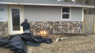 Adding rock to cover old stucco on the front of our 100 year old farm house. Here it is with Joe grouting.