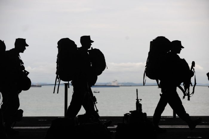 service members with packs walking