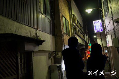 夜の路地裏を歩く男女