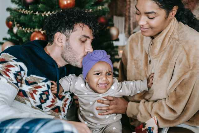 cheerful multiracial family with crying baby near christmas tree