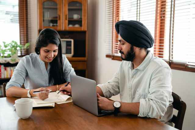 smiling spouses discussing business plan at home
