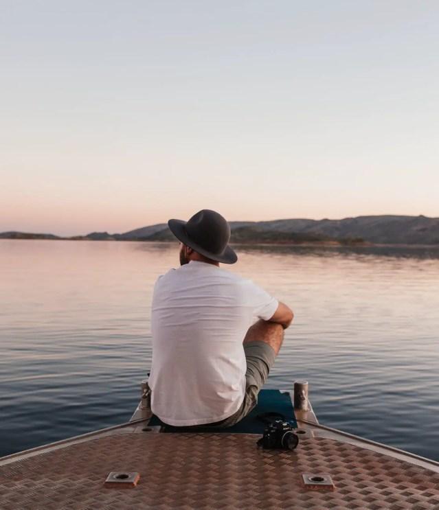 man sitting on dock near rippling water at sunset