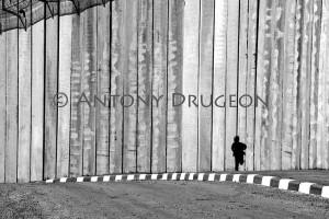 Un petit garçon (5 ans) court le long du mur de séparation israélien haut d'environ 10 mètres.