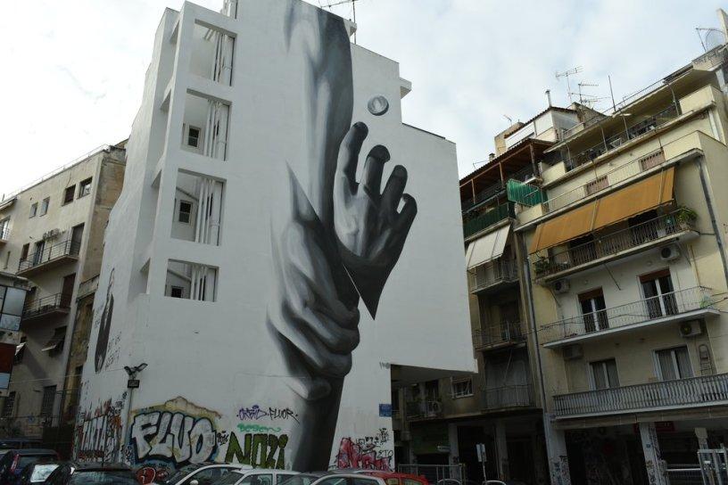 Fresque géante sur un immeuble d'Athènes, représentant une main secourant une autre