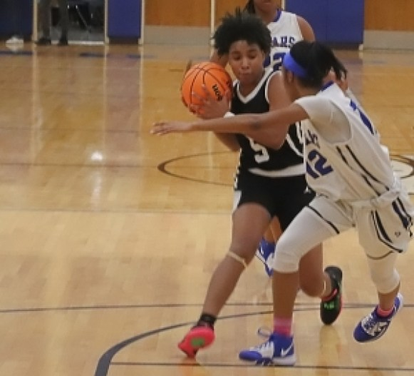 Stephenson's Kassidy Broussard (12) cuts off a drive by Martin Luther King's Ashlynn Green (5) during the Lady Jaguars 57-51 comeback win. (Photo by Mark Brock)