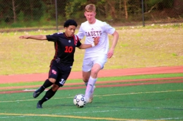 Druid Hills Dani Bibiano (10) maneuvers against Benedictine's Nick Dillon during first half action of the Red Devils 2-0 upset of the 10th ranked Cadets. (Photo by Mark Brock)