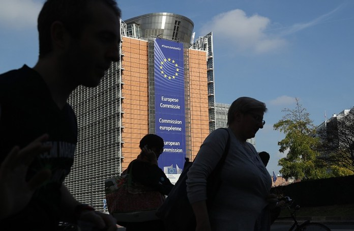 BRUSSELS, BELGIUM - OCTOBER 17: People walk past the Barleymont building of the European Commission on October 17, 2018 in Brussels, Belgium. British Prime Minister Theresa May is to address the assembled 27 European Union leaders on the progress of Brexit negotiations at a working dinner tonight at the European Council. The leaders will also meet tomorrow for a summit to discuss negotiations on the deepening of the Economic and Monetary Union as well as migration and internal security. (Photo by Sean Gallup/Getty Images)