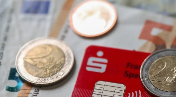 Some banknotes and coins are seen together with a credit card with an integrated NFC technology chip for cash-less payment in a shop in Frankfurt am Main, Germany, 12 February 2019. Later on 12 February the German Federal Bank 'Bundesbank' will present the results of a study 'on Costs of cash payments in retail trade'. EPA/ARMANDO BABANI