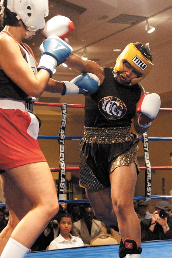 Buckhead accountant Lori Williams-Jones, right, throws a punch during a boxing match.