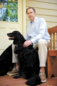 Hugh Penn with Banjo, one of his two dogs. Penn's home in northeast Sandy Springs is easy to spot. It's the one marked by an American flag.