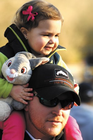 B.J. Kelly gives his daughter Lyla, 2, a bird's eye view as they watch Lands Kelly, 4, being introduced during opening day ceremonies of spring baseball at Murphey Candler Park on March 8 in Brookhaven.