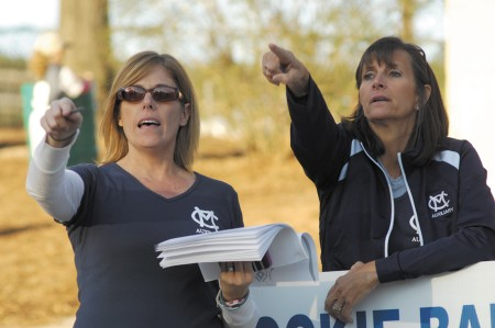 Volunteers Kathleen Jackson, left, and Brenda Kidwell, survey the action at Murphey Candler Park in Brookhaven during the start of Murphey Candler Baseball's season.
