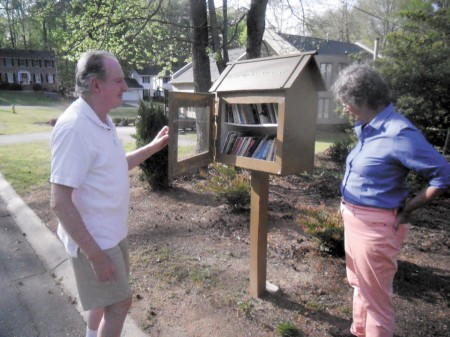 Ronald Pennington, left, and his wife, Joan Warren, with their bookbox on Martina Drive.