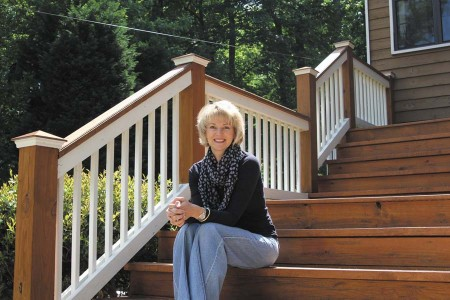 Melissa Chevalier sits on the steps of her Pine Hills home.