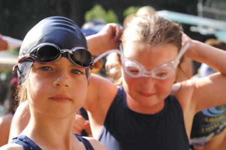 """Lauren Foglesong, left, and Ansley Freudenstein, teammates on Chastain Park's """"Tidal Waves"""" swim team, get their game faces and goggles on before a swim meet against The Branches' """"Gators"""" in Dunwoody on June 4."""