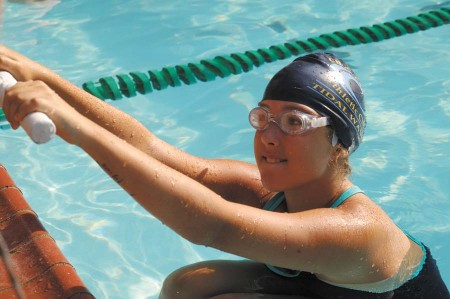 Lizzie Wright, a member of the Waves' relay team, gets ready for the first leg. Below, right, the meet was held at The Branches Club pool.