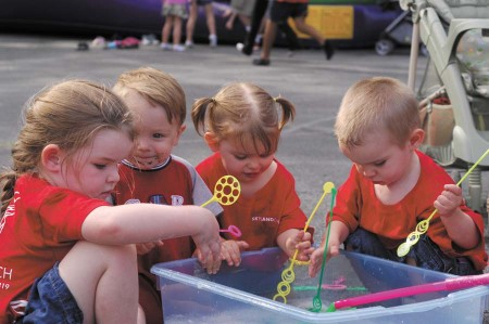 From left, Madison Sanders, 4, Sam Wages, 1, twins Liberty Sanders, 1, and her brother Jackson, enjoy making bubbles at Skyland United Methodist Church's neighborhood block party on June 1.